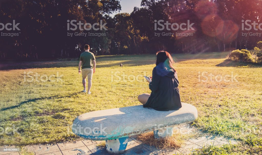 Breakup of a couple with guy leaving and sad girlfriend staying on the bench stock photo