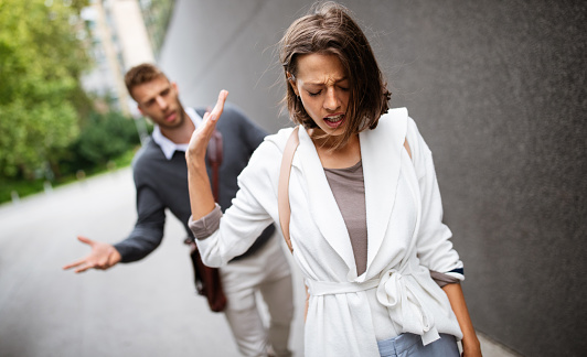 Breakup of a couple with man and sad girlfriend outdoor. Divorce, couple, love, pain concept.