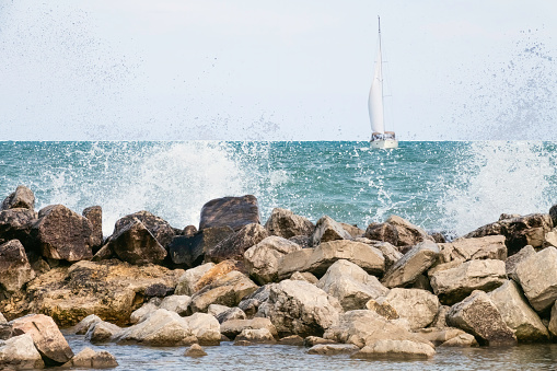 Breakwall in the path of a sailboat on Lake Michigan