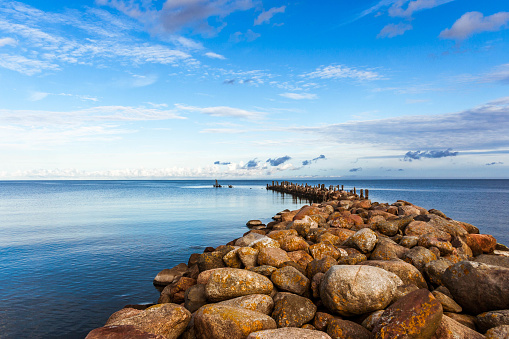 Breakwater in calm, blue Baltic sea on a sunny day.
