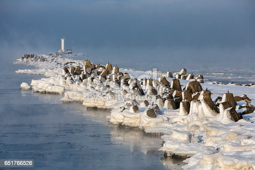 An iced breakwater of embouchure of Daugava  and a lighthouse in the end of it