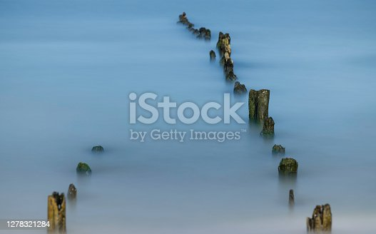 sea waves gently swapping on the wooden breakwater
