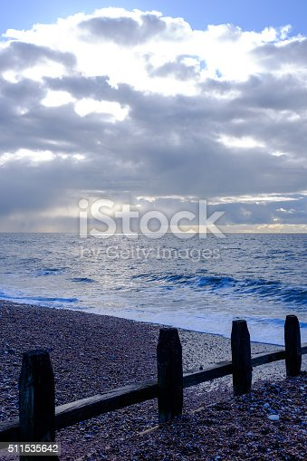 protective barrier structure on the sea shore made of wood and iron bolts leading into the sea on a pebbly beach with moody clouds and sunshine
