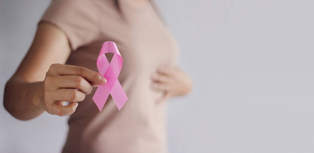breast cancer awareness concept. health care and medical. hand of woman holding pink ribbon awareness symbol for endometriosis, medicine. prevention breast. - różowy zdjęcia i obrazy z banku zdjęć