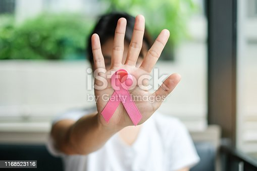istock Breast Cancer Awareness, Woman hand holding Pink Ribbon for supporting people living and illness. Women Healthcare and World cancer day concept 1168523116
