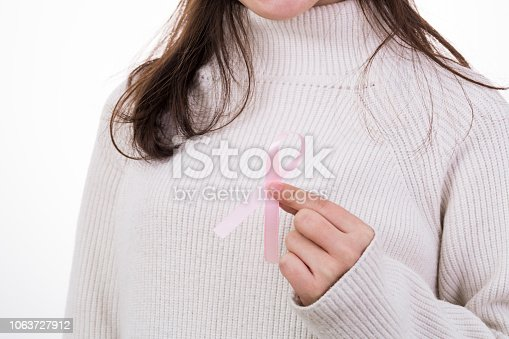 istock Breast Cancer concept. Pretty young woman holding pink breast cancer awareness ribbon 1063727912