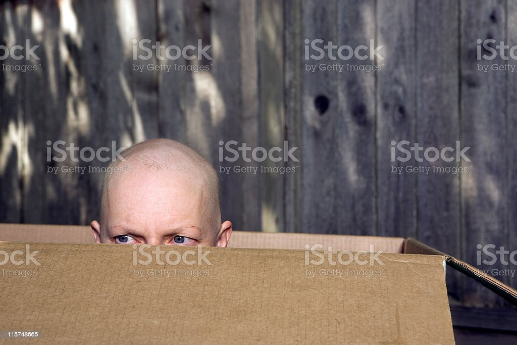 Breast cancer patient looking out from a cardboard box. royalty-free stock photo