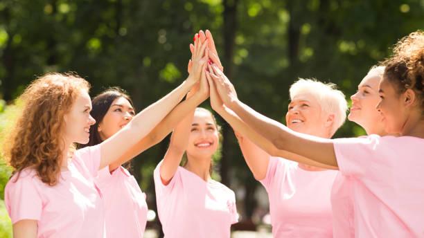 borstkanker vrijwilligersgroep van multi-etnische vrouwen geven hoog-vijf buiten - breast cancer stockfoto's en -beelden
