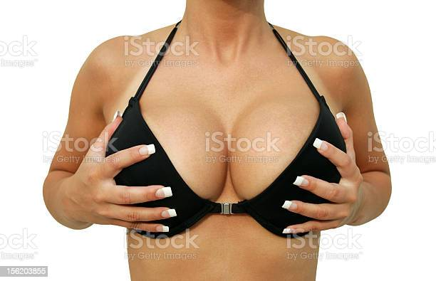 closeup of a woman in bikini is holding her made breasts, isolated.