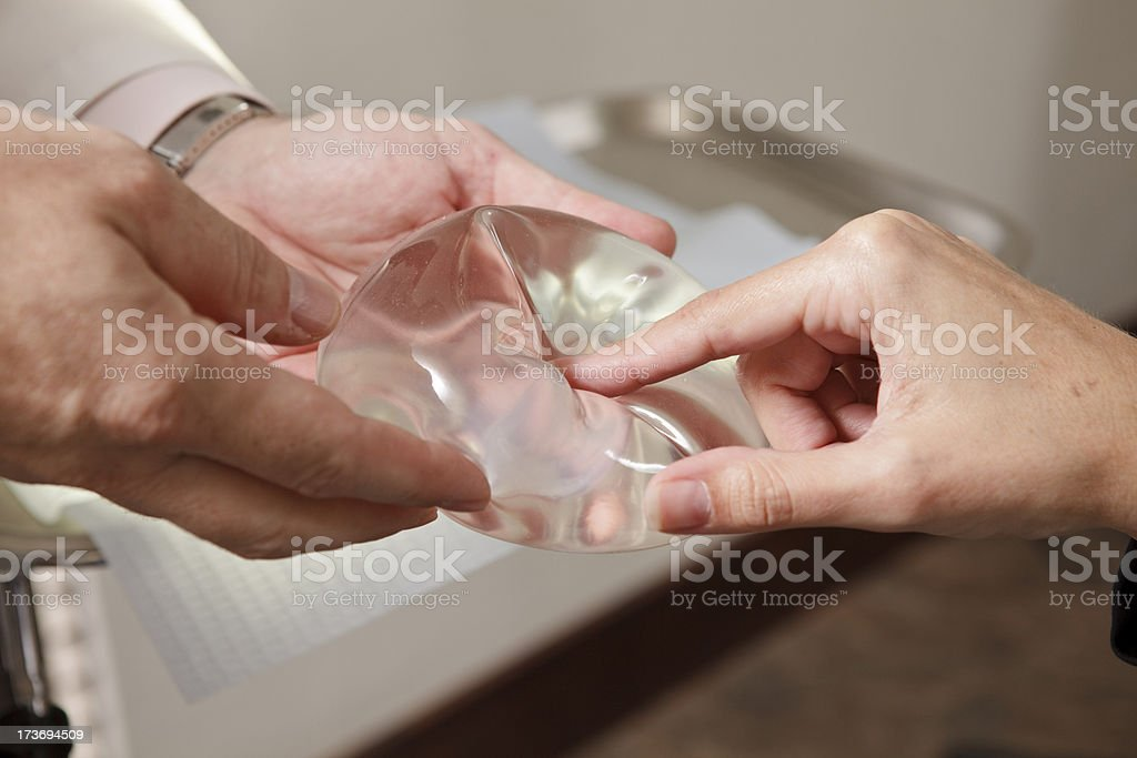 Breast Implants Being Shown to Patient A doctor shows a patient breast implant options. Adult Stock Photo