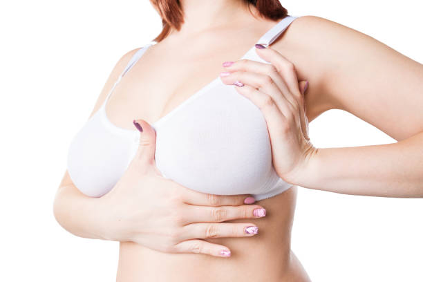 Breast test, woman examining her breasts for cancer, big natural boobs isolated on white background stock photo