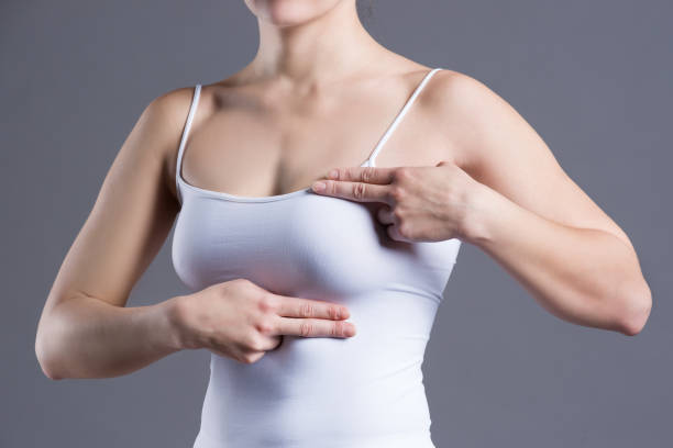 Breast test, woman examining her breasts for cancer, heart attack, pain in human body stock photo