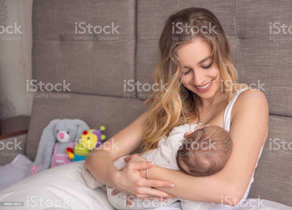 Amamantar al bebé. Bonita Madre sosteniendo a su hijo recién nacido. Sonrisa de madre y lactante. Hermosa mujer y el amor recién nacido en casa. Madre rubia mama alimentación al bebé. - foto de stock