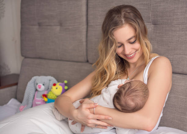 Breastfeeding baby. Pretty mother holding her newborn child. Mom smile and nursing infant. Beautiful woman and new born love at home. Blond mother breast feeding baby. stock photo