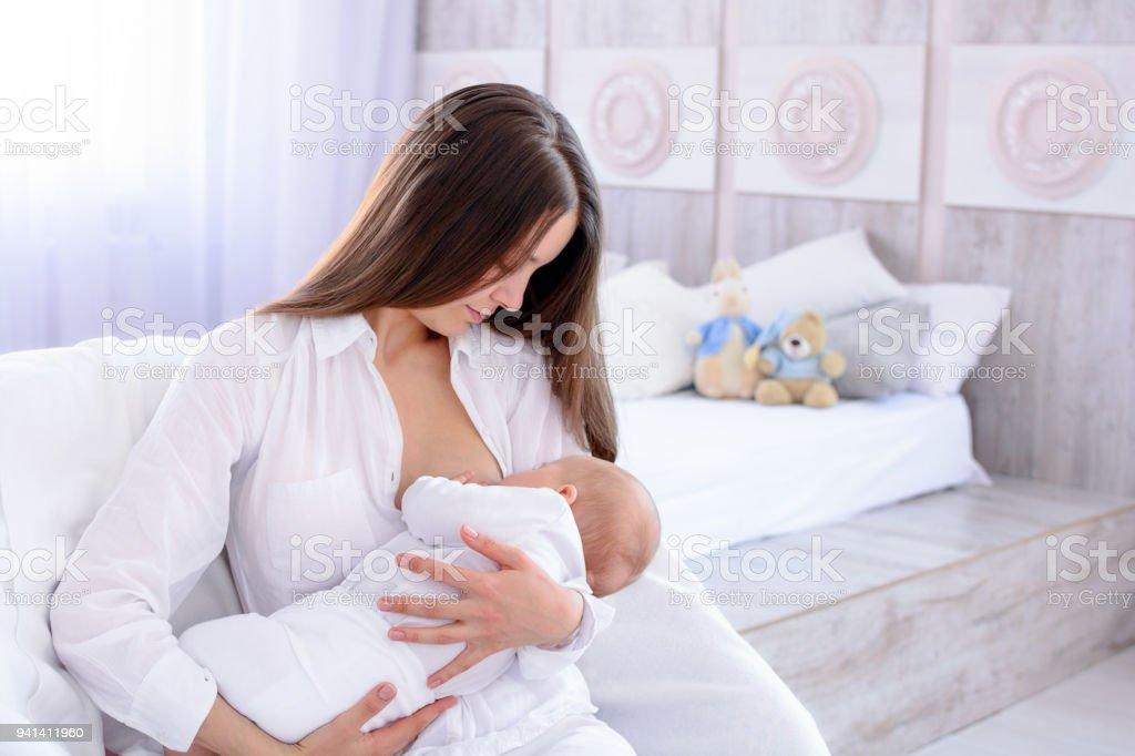 Amamantar al bebé. Joven madre sostiene y amamanta a su hijo recién nacido. Mujer y niño recién nacido en el dormitorio blanco. Luz interior. Ropa blanca. - foto de stock