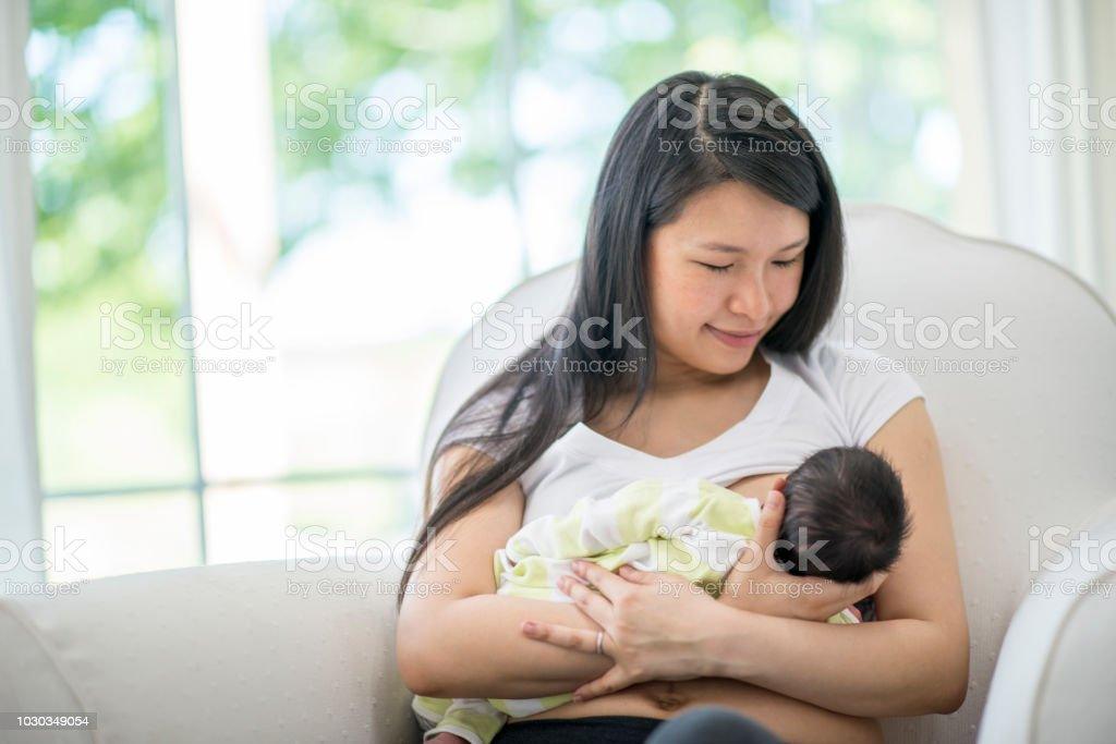 Young Mother Breastfeeding Her Baby Girl At Home High-Res