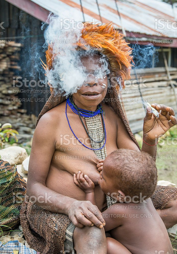 breastfeeding mother smoking a cigarette stock photo
