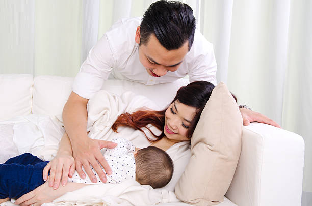 breastfeeding - woman breastfeeding husband stock photos and pictures