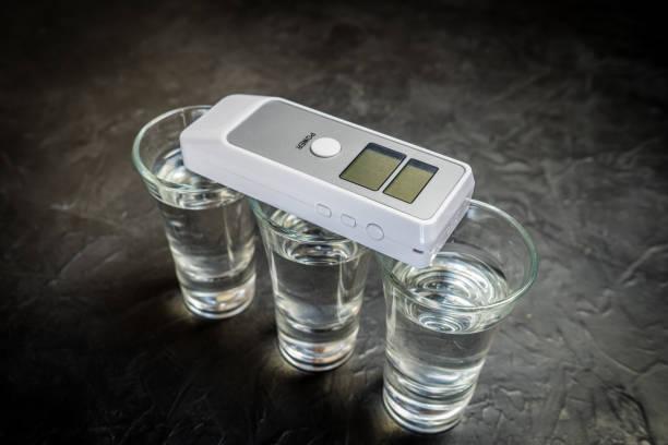 bafômetro e álcool em um copo. foto em um fundo escuro. - bafometro - fotografias e filmes do acervo