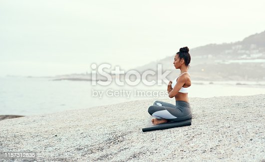 Shot of a sporty young woman practicing yoga at the beach