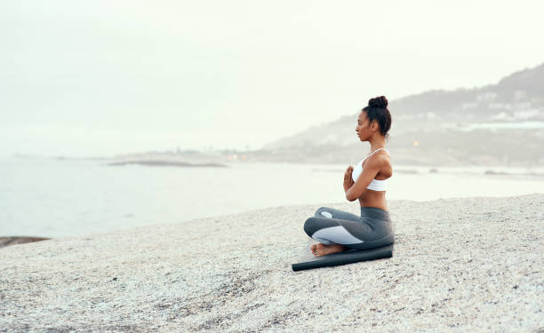Breathe a fresh sense of purpose into your life Shot of a sporty young woman practicing yoga at the beach prayer pose yoga stock pictures, royalty-free photos & images