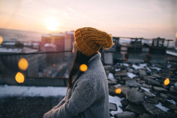 Breathe Young woman enjoying in the view of winter sunset from building rooftop city break stock pictures, royalty-free photos & images
