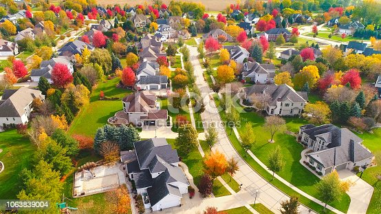 Breathtaking aerial view of idyllic neighborhoods richly colored with colorful Autumn trees.