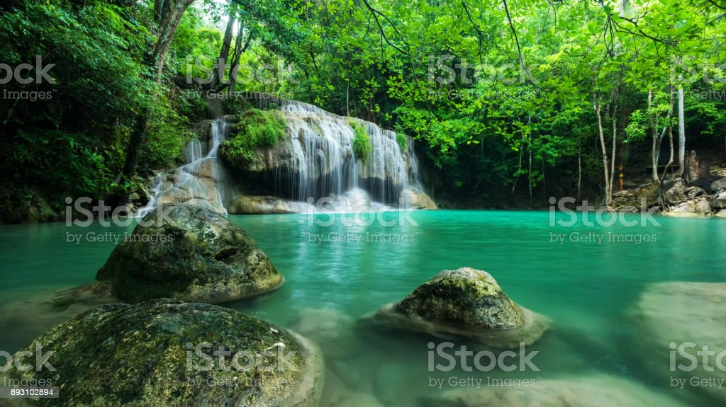 Breathtaking green waterfall at deep forest, Erawan waterfall located Kanchanaburi Province, Thailand stock photo