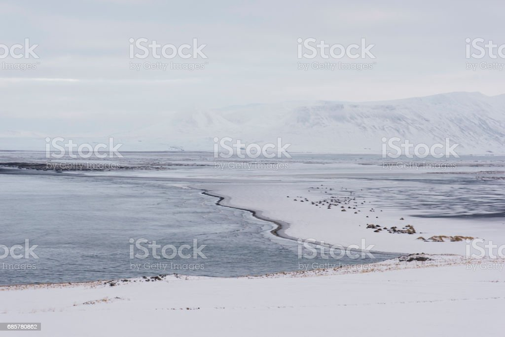 Breathtaking panoramic view on Vatnsnes peninsula, winter snowy frozen shore with the ocean and mountains on the background royalty-free stock photo