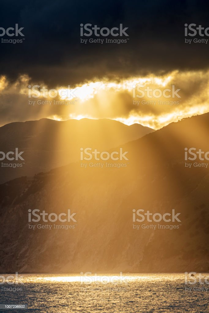 Breathtaking sunbeamsbetween the clouds, mountain and sea stock photo