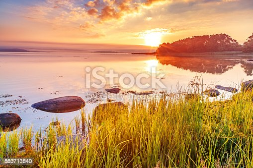istock Breathtaking sunrise scenery, View at Sweden coastline covered with green grass over Northern Sea at dramatic dusk sky and sun touched horizon. Wallpaper landscape in red - green - orange color tones. 883713840