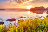 Breathtaking sunrise scenery, View at Sweden coastline covered with green grass over Northern Sea at dramatic dusk sky and sun touched horizon. Wallpaper landscape in red - green - orange color tones.