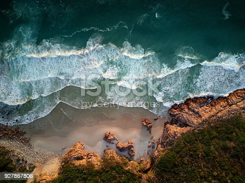 istock Breathtaking view from above of waves crashing on the beach and rocky shore 927867806
