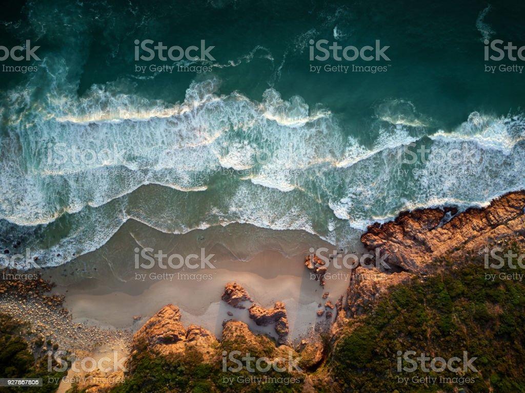 Atemberaubenden Blick von oben auf Wellen an den Strand und das felsige Ufer – Foto