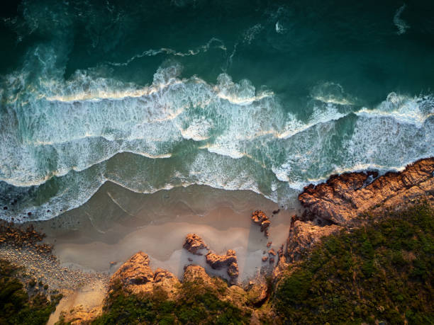 Breathtaking view from above of waves crashing on the beach and rocky shore stock photo