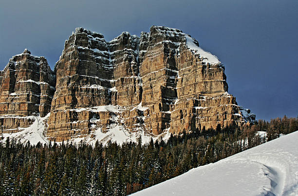 Breccia Peak and Cliffs in winter next to snowmobile tracks stock photo