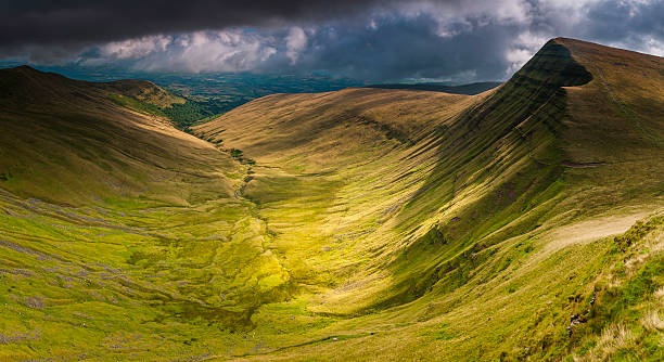 Brecon Beacons National Park dramatic mountain panorama peaks valleys Wales The steep slopes and rocky ridges of Cribyn and Bryn Teg overlooking the grassy valley of Cwm Sere dotted with sheep under dramatic stormy skies deep in the Brecon Beacons National Park of Wales, UK. ProPhoto RGB profile for maximum color fidelity and gamut. south wales stock pictures, royalty-free photos & images