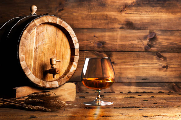 Brendy glass and old oak barrel Brendy glass and old oak barrel brandy stock pictures, royalty-free photos & images