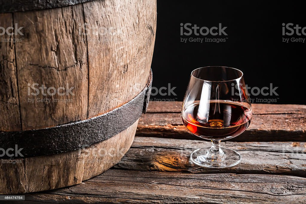 Brendy glass and old wooden barrel stock photo