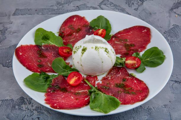 bresaola with cheese pecorino and arugula. bresaola and arugula salad. - bresaola foto e immagini stock