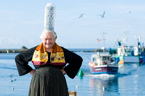 breton women with headdress breton women with headdress posing on a harbor in brittany with fisher boat bonnet stock pictures, royalty-free photos & images