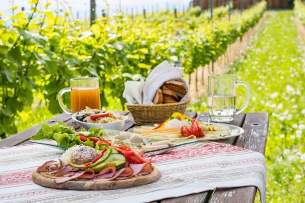 Brettljause, kalte Platte mit Mahlzeit auf Holztisch im Weinberg – Foto