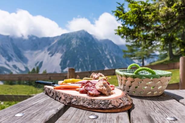 Brettljause auf Holztisch mit Blick auf den Gebirgszug Karawanken – Foto