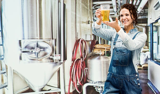Brew master with beer glass in place of work stock photo