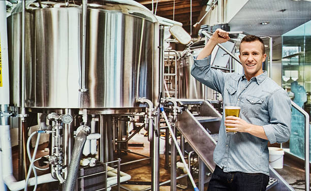 Brew master with beer in place of work stock photo