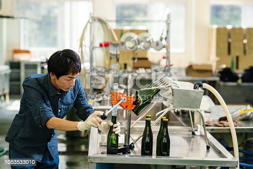 Brew mater bottling his product in a small batch craft beer brewery in Japan