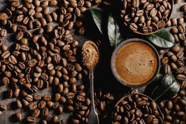 Brewed black coffee and beans in arrangement Top view of cup of brewed black coffee arranged with plenty of brown beans and green coffee leaves. caffeine stock pictures, royalty-free photos & images