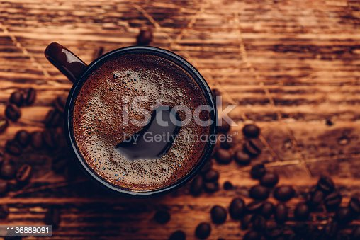 Brewed black coffee in metal mug over wooden surface