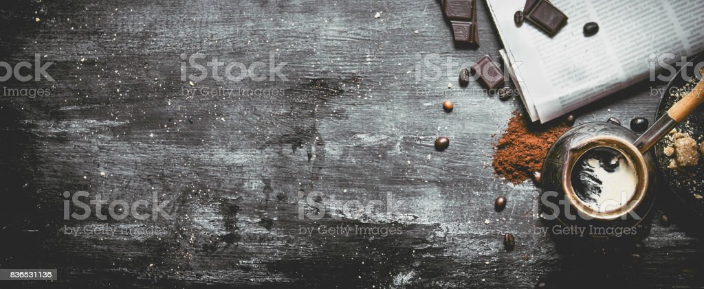 Brewed coffee pot with fresh newspaper and bitter chocolate. stock photo