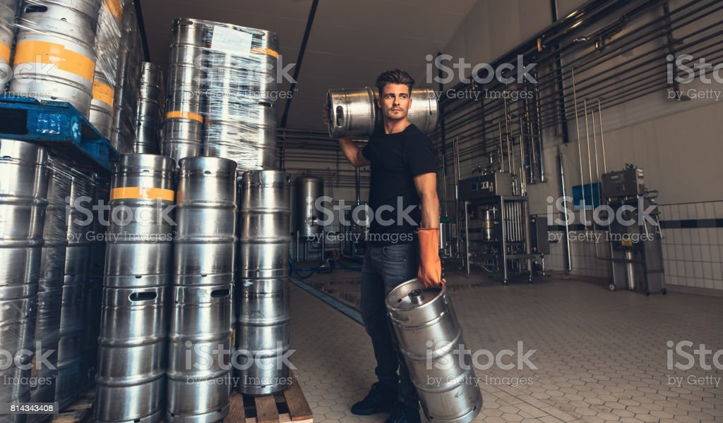 Brewer carrying keg at brewery factory stock photo